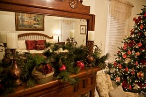 Bed reflected in a Christmas pine decorated mantel mirror with nearby Christmas tree