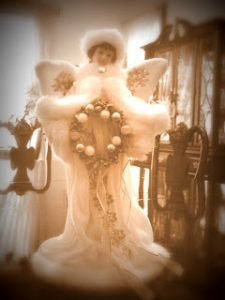 sepia picture of a white angel holding a wreath