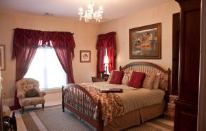 King sized bed with tan covers with burgundy accessories and drapes