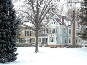 snowy-landscape-two-story-blue-Victorian-home