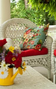 White wicker porch chair with colorful cushions and floral arrangement