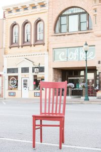 The red chair in front of SoapCo Coffee House and Our Town Books, two-story vintage storefronts