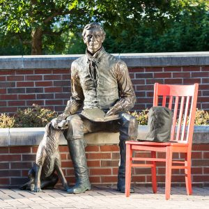 photo of the Red Chair Travels chair next to the Abraham Lincoln with a Dog bronze statue on the Illinois College Campus in Jacksonville Illinois