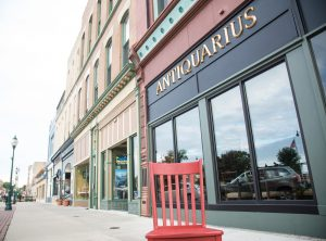 Red chair in front of Antiquarius and other shops and restaurants in a row of vintage storefronts