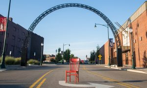Red chair in the middle of the street in front of the iron archway on North Main Street