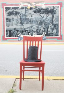 Red chair in front of Wall Dog painting of Abraham Lincoln addressing the crowd