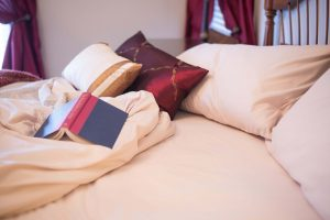 Unmade bed with creamy linens, open hard cover book and decorative pillows