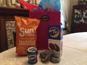 Eclipse snacks including sun chips, Eclipse gum, Moon pies and red bag on a dining room table in front of the fireplace