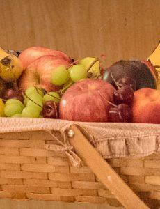 basket of fresh fruit including apple, grapes, plum