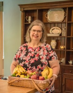 Innkeeper-Gwenn-with-basket-of-fresh-vegetable-in-front-of-wood-cabinet