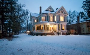 Lights glow in the snow covered Blessings on State Bed & Breakfast, a vintage Victorian mansion in Jacksonville Illinois