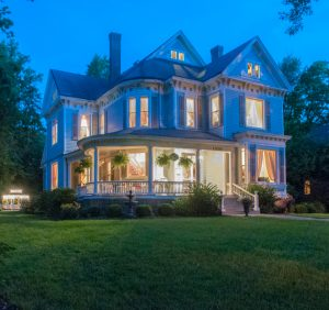 Lights glow from the windows and illuminate the boston ferns hanging on the front wraparound porch in this evening photo of Blessings on State Bed & Breakfast a Victorian mansion in the historic district