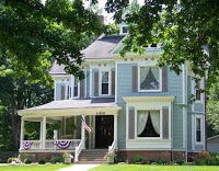 Blessings on State Bed & Breakfast, a light blue Victorian mansion with cream trim and gray shutters with patriotic bunting and flag