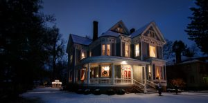 well-lit snowy Victorian home with porch lights on and blue night sky