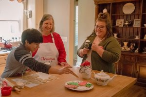 Two women and a boy decorating Christmas cookies at kitchen table