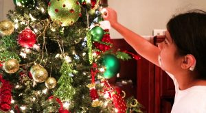 Young person putting Christmas decorations on Christmas tree