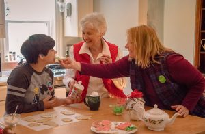 women and boy decorating Christmas cookies