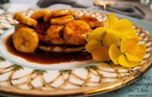 Bananas Foster Pancakes on a china plate with yellow pansy garnish