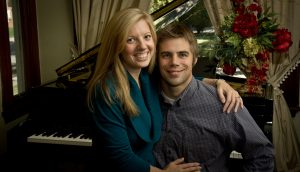 couple pose in front of grand piano