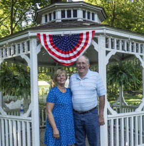 older couple stand in front of patriotic gazebo