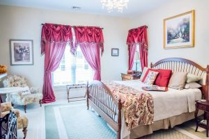 Luxury bedroom with king size bed with neutral color pillow and chairs and burgundy drapes