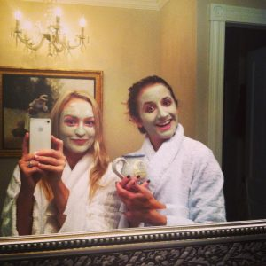 two girls with facials posing in front of mirror