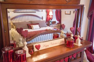 Valentine hearts in front of mantel mirror reflecting king bed