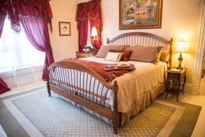 Large room with green area rug king sized bed with burgundy accessories