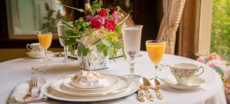 beautiful place setting with meringues juice and water with flowers in background