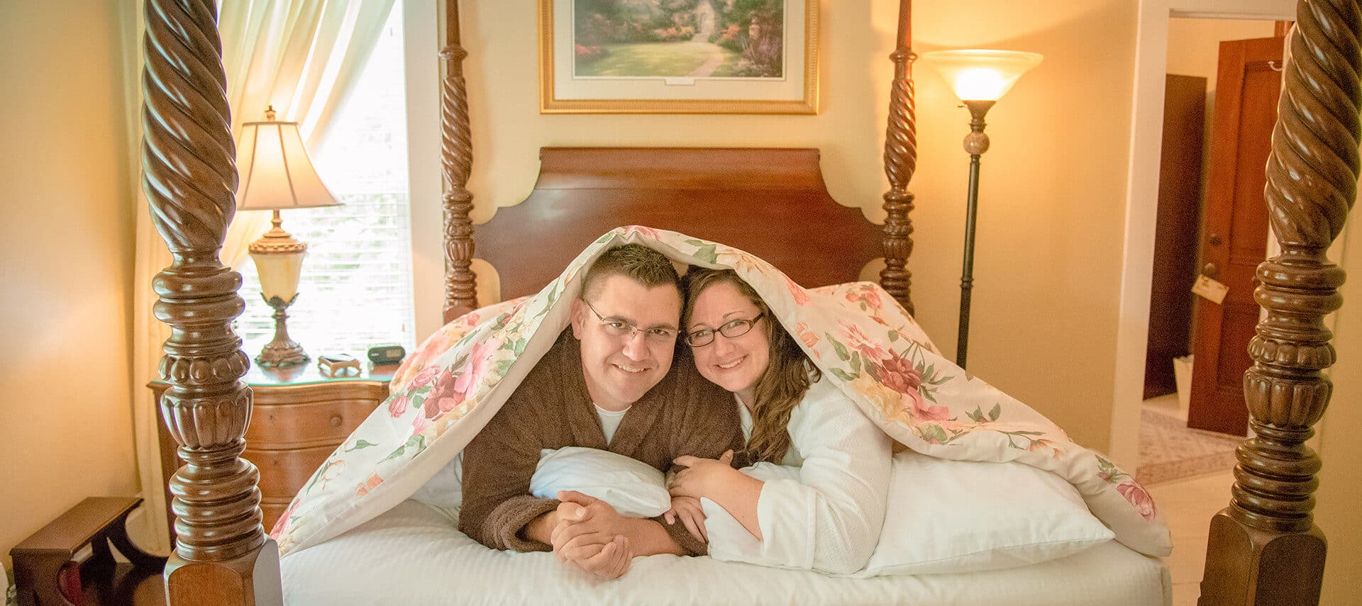 couple in robes looking out under covers