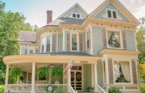 Exterior blue two story Victorian home with cream colored wraparound porch