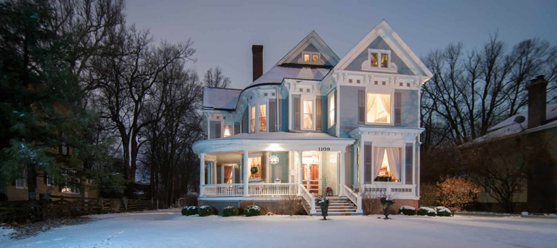 snow covered blue two story Victorian home