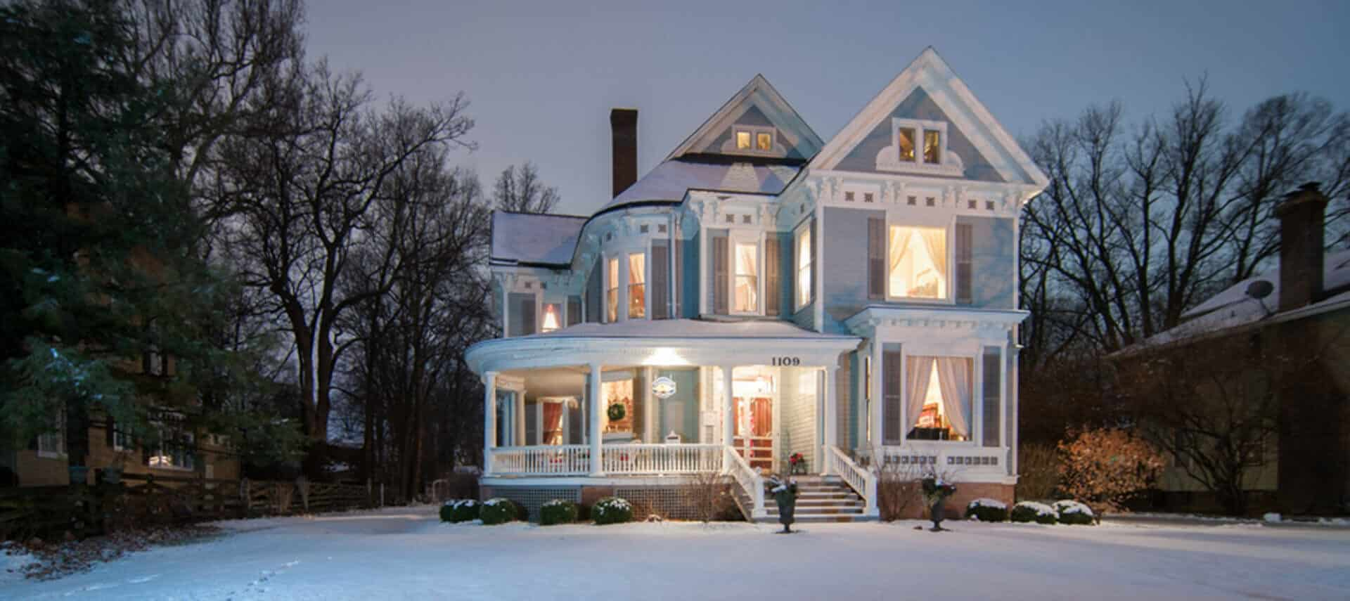 lights illuminate a vintage blue mansion