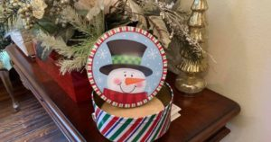 tin of fudge in front of Christmas greenery and flowers