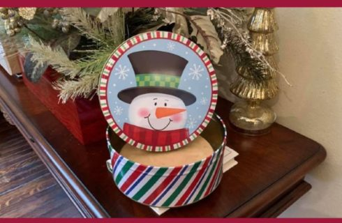 snowman tin with peanut butter fudge in front of Christmas decor