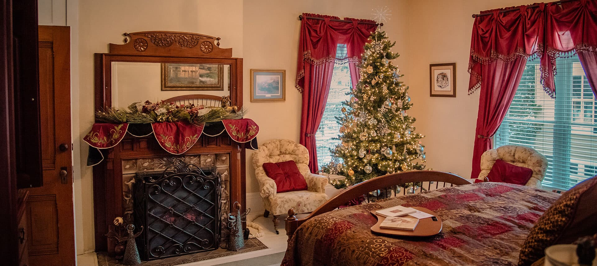 decorated mantel and bed with burgundy decor and Christmas tree