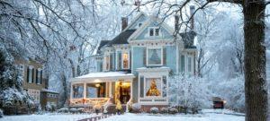 Christmas lights shine around a snowy story blue Victorian home
