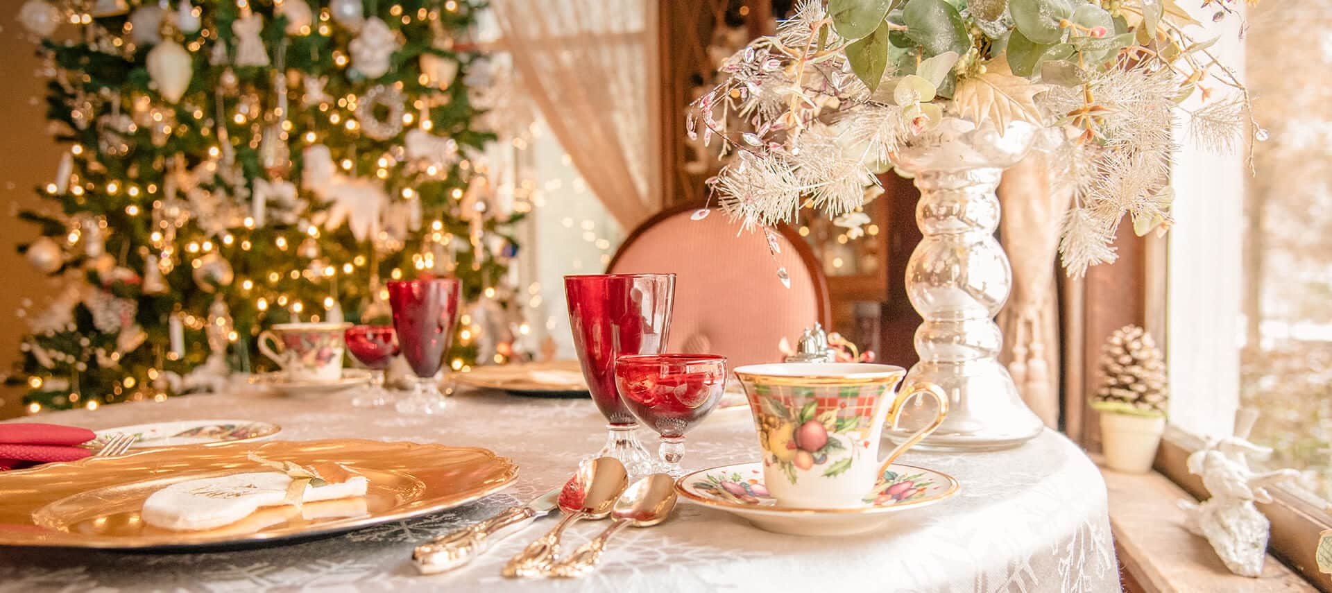 Table setting with Christmas china and red glasses