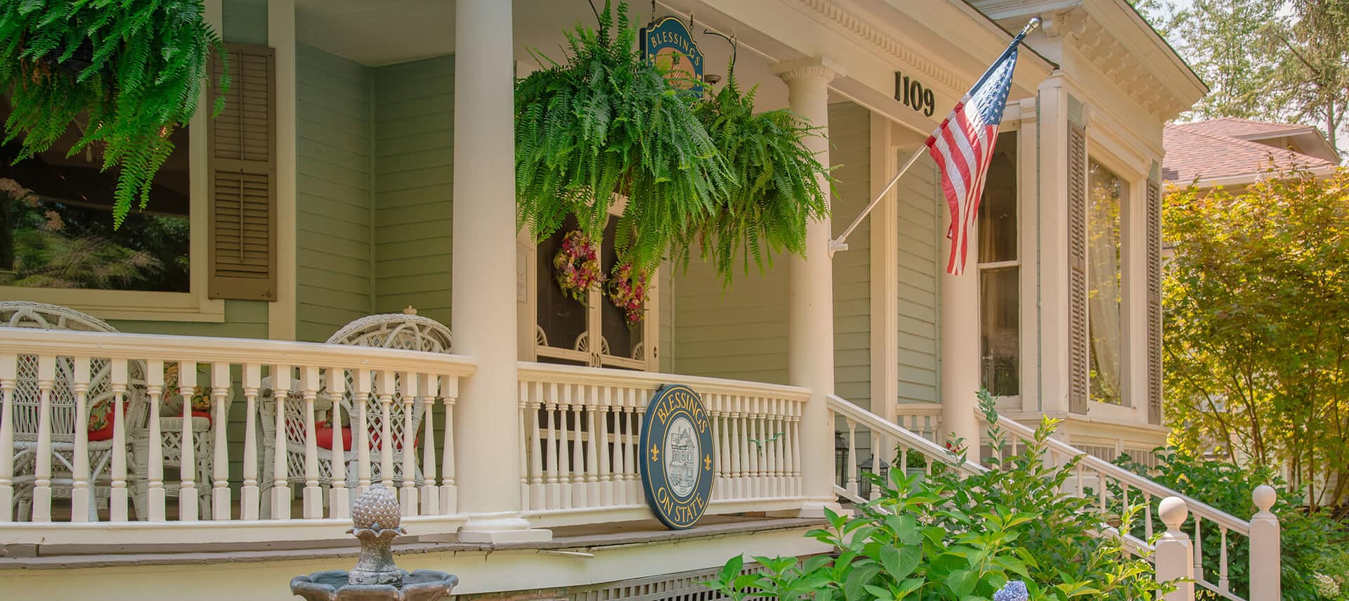 white porch with hanging Boston ferns and blue sign
