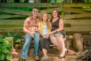 dad daughter and mom sitting on a garden bench in front of a wooden fence