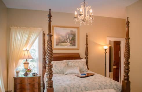 Dark wood four poster bed with blue comforter and dark wood dresser