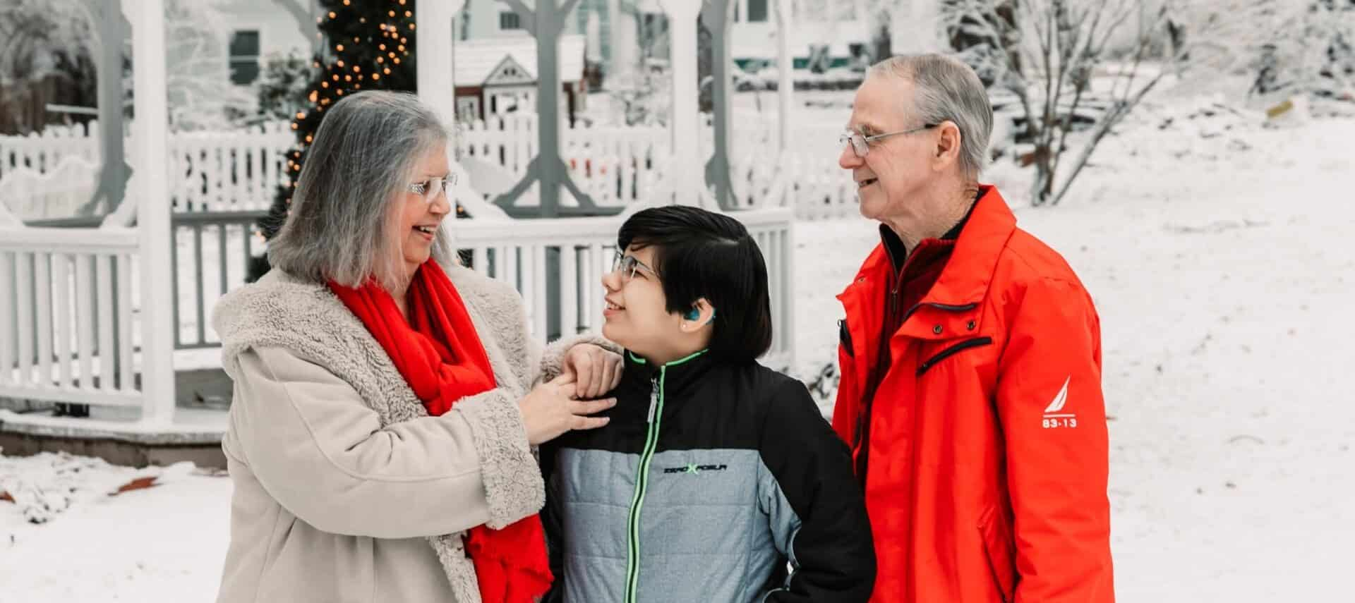 grandparents with grandson in snowy yard