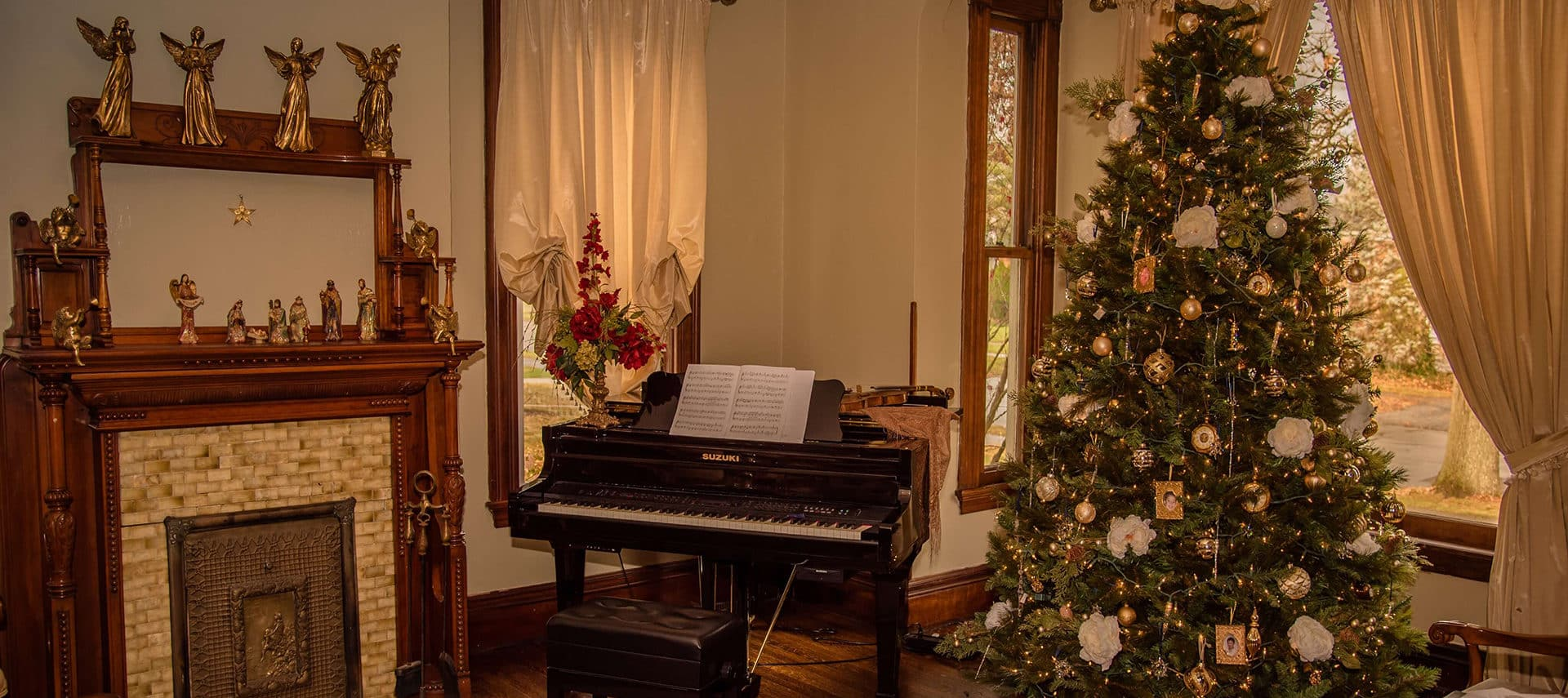 festive fireplace angels grand piano and decorated Christmas tree
