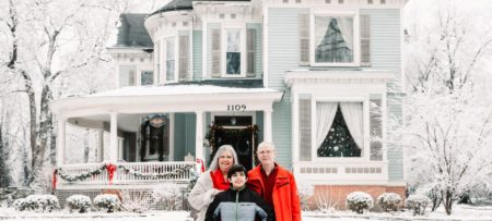 Innkeeper mom dad and son pose in front of snowy blue Victorian home with white columned porch