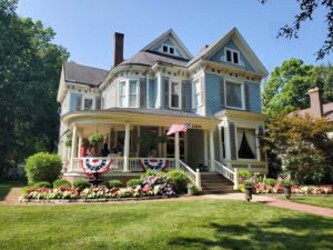 Blue two-story Victorian home with bunting and American flag