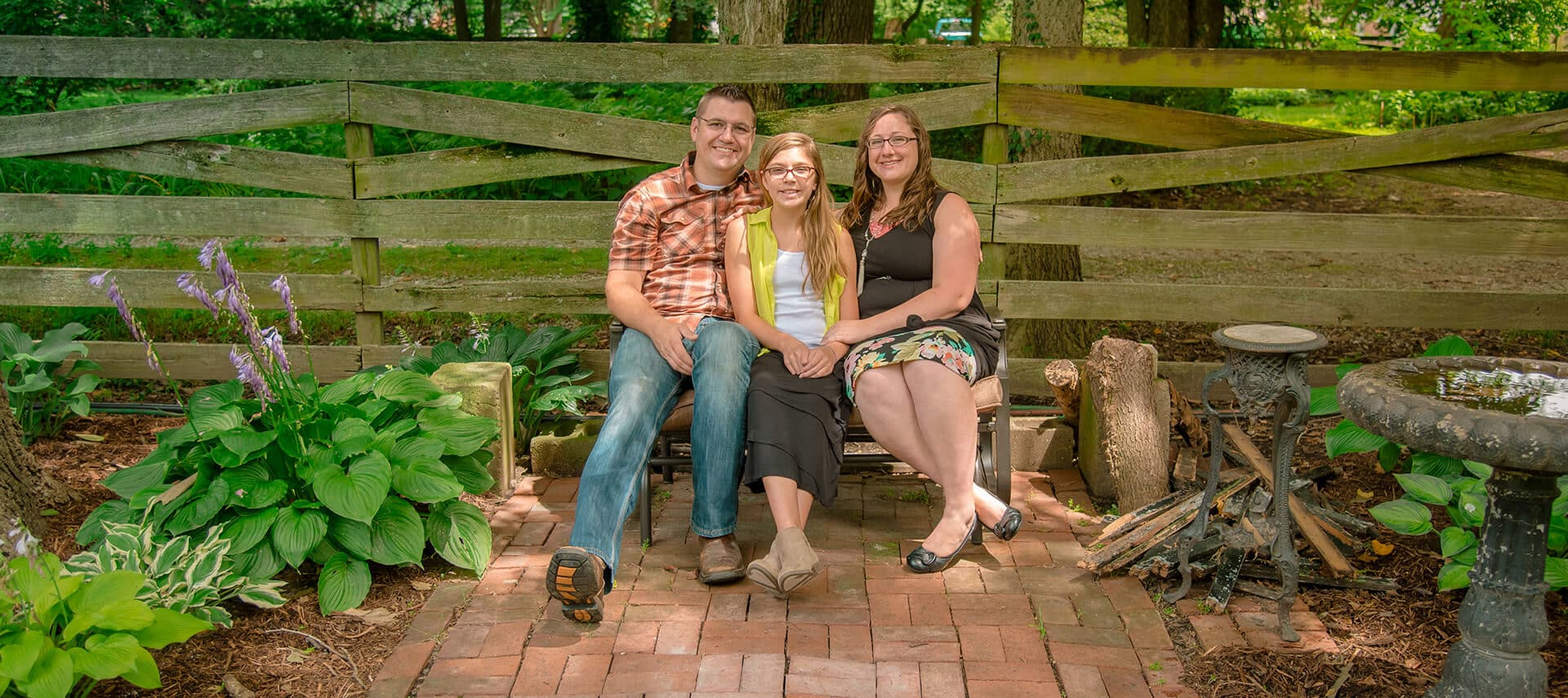 Father daughter and mother sit on park bench