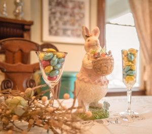 Pastel colored bunny and Easter decor including colorful cadies in a china goblet