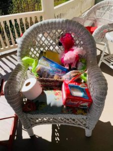 Toilet paper frozen cake and flamingo toy in white wicker porch chair with blue floral cushion