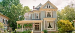 Two story blue home with cream colored wraparound porch