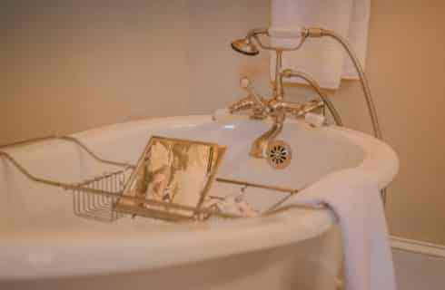 white soaking tub with white towels and chrome bath tray with mirror